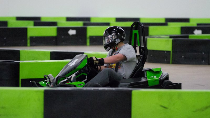 The man is going on the go-kart on karting track indoors.