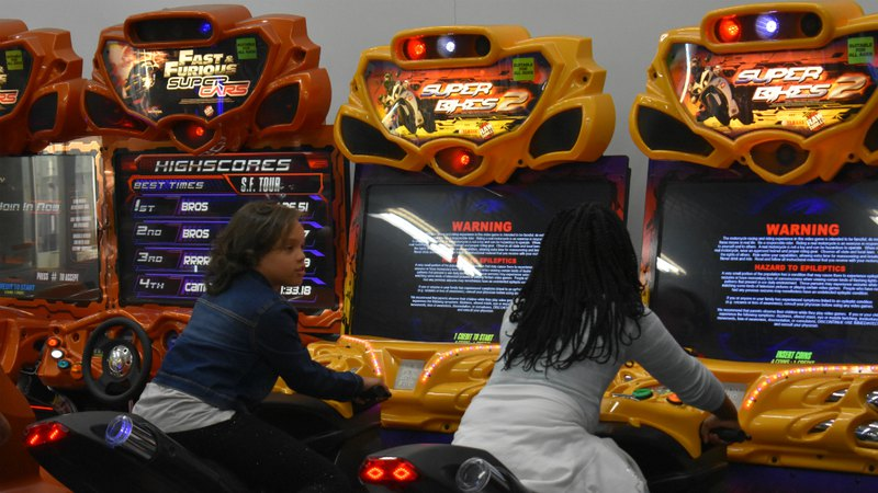 Girls playing racing simulator arcade game at family fun center