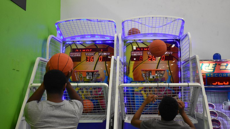 Boy and man playing Basketball Shooting Arcad Game