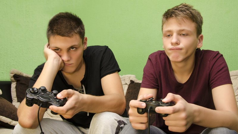 Bored teenagers playing video games