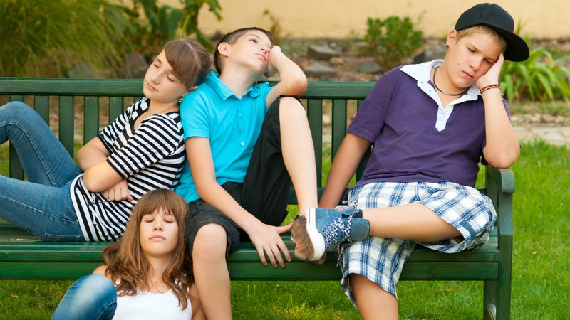 Bored teenagers resting on the bench on summer day