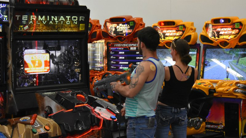 A couple playing arcade games | Speed Raceway entertainment center